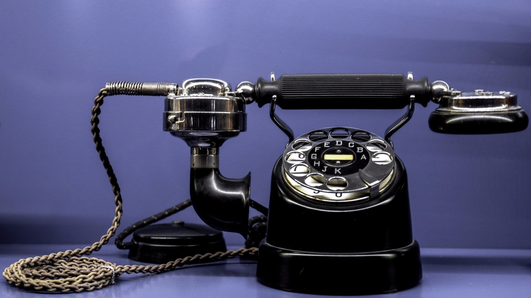 [Image Description: A vintage, black rotary phone sits in front of a solid background, with the handset resting evenly across the housing. A braided cord connects the handset to the housing.]