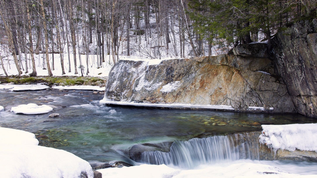[Image Description: A view across a small flowing brook in a snowy Vermont winter forest. A large, bare-sided. sheer rock face rises a short height from the water, along the far side of the stream, with coniferous and deciduous trees growing atop and behind it. A few patches of snow and ice float on the brook as it flows from the left to the right of the shot. In the foreground of the cliff face, near the bottom-right of the shot, is a wide, single cascade in the blue-green water, creating wintry foam at the edge of the frame.]