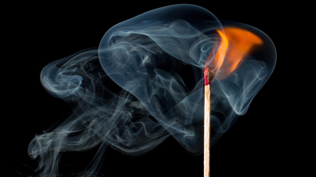 [Image Description: A single, lit match is standing vertically, right of center in the frame. Smoke from the match is curling around the match stick and drifting to the left.]