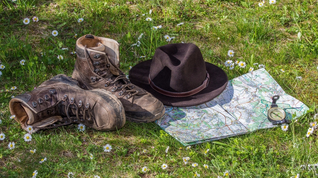 [Image Description: A grassy field, speckled with fragile,white, wild daisies. On the grass, from left to right: a pair of worn-in hiking boots, with the right boot lying on its side; a black fedora hat with a sewn leather band; a partially-unfolded map tucked just under the toe of the left boot and the brim of the hat; a small metal compass rests on the map, near the bottom-right.]