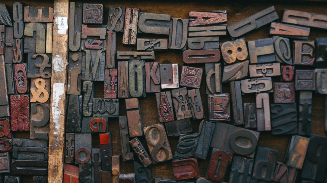 [Image Description: an assortment of alphanumeric characters and symbol stamps are messily arranged on a wooden surface. They are in a wide array of fonts and sizes.]