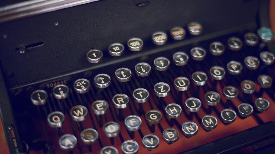[Image Description: A well-maintained, antique typewriter keyboard with circular, lever-action keys, capital letters emblazoned in white on each black key, sprawls diagonally across the shot and fills the frame.]