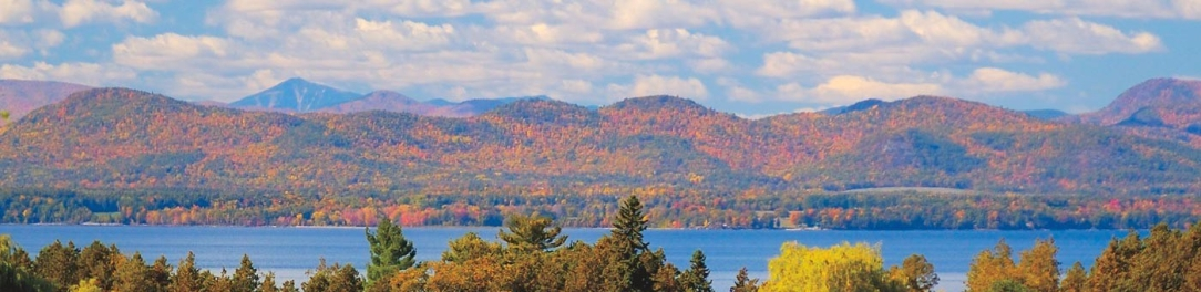 [Image Description: A view across Lake Champlain, over the tops of some trees that are just starting to turn their leaves into the autumn hues of red, orange and yellow instead of green. Across the lake, various mountains rise, each covered with leaves that are largely set in autumn tones, creating a multicolored collage. In the sky, many large, solid white clouds of some variety I can't name are seen]