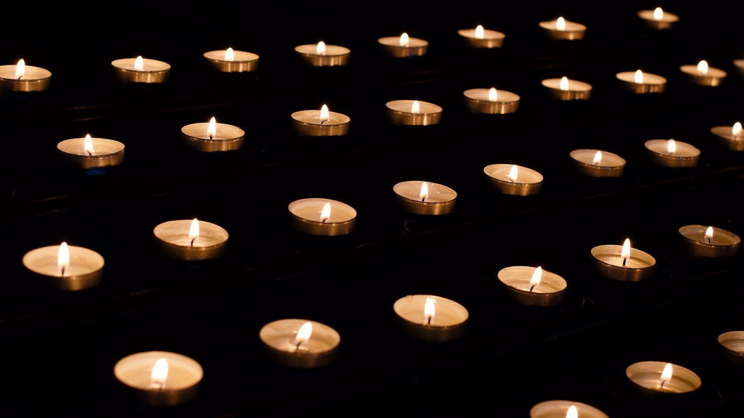 [Image Description: five rows of tealight candles, light, cross the frame nearly horizontally, though the photo is taken at a slight angle. The field of the photo is solid black, as though in profound darkness.]