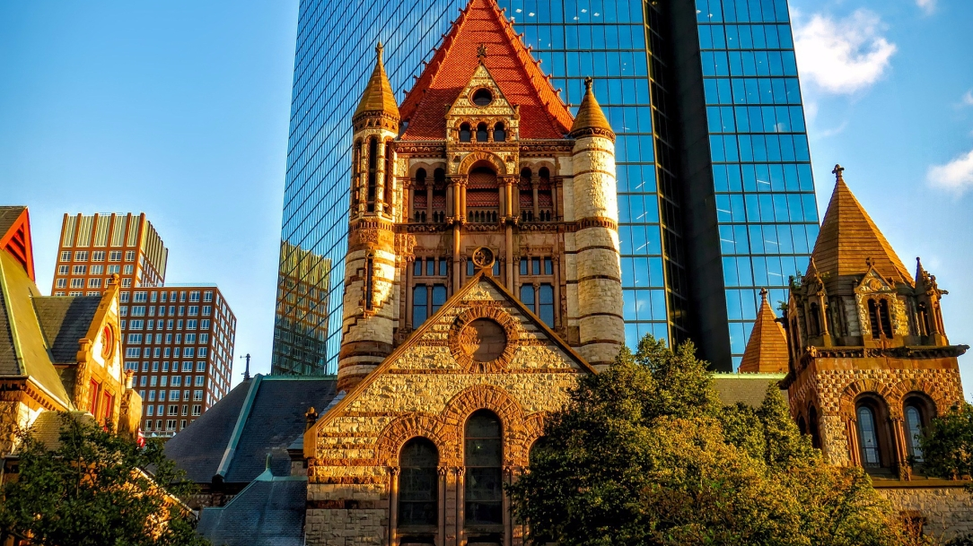 [Image Description: Historic light-stone Trinity Church in downtown Boston is seen behind a deciduous tree which is covered in green leaves. Behind the tower and/or steeple of the stone house of worship rises the glass-sided high rise of the John Hancock Tower. In the background of the left side of the picture, above a small building attached to the left side of Trinity church, rises another tall, square, brick building.]